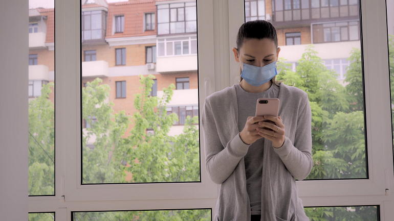Woman in blue face mask looking at mobile phone