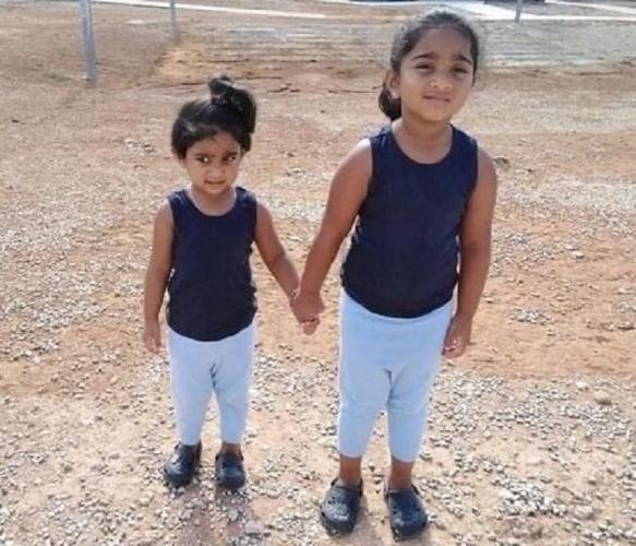 Five year old Kopika Murugappan and her sister Tharunicaa in a detention centre yard