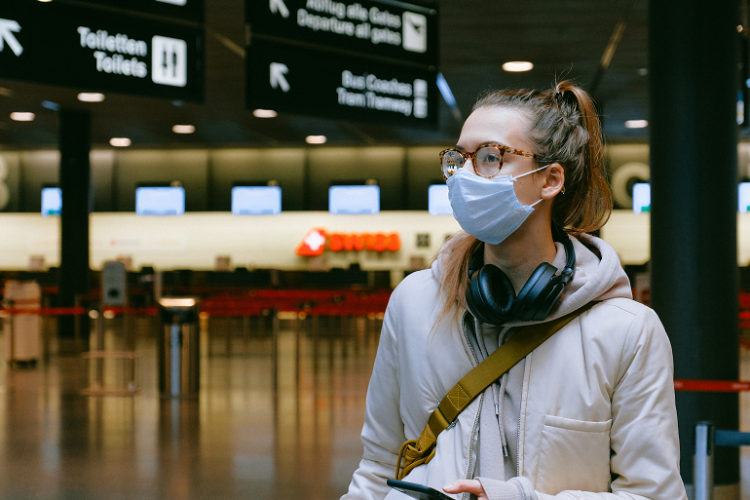 Woman wearing a surgical mask while travelling through airport